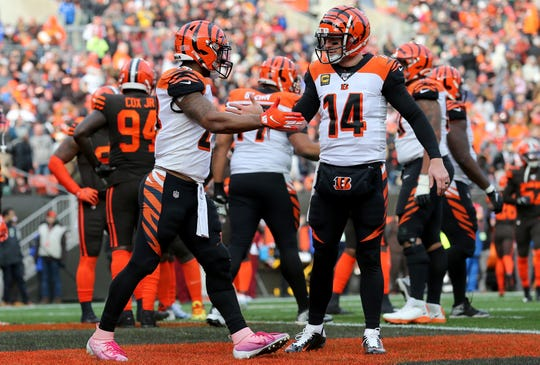 Cincinnati Bengals running back Joe Mixon (28) and Cincinnati Bengals quarterback Andy Dalton (14) shake hands after Mixon's touchdown run in the second quarter during a Week 14 NFL football game against the Cleveland Browns, Sunday, Dec. 8, 2019, at FirstEnergy Stadium in Cleveland.
