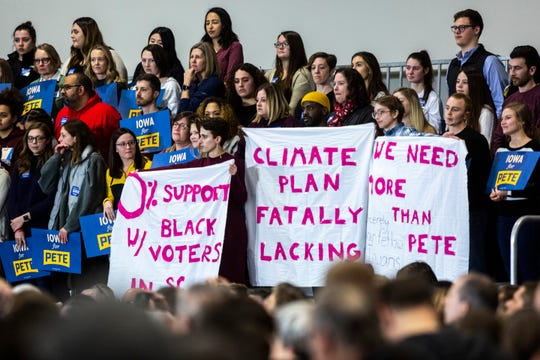 Protesters hold up sheets of fabric as Democratic presidential candidate Pete Buttigieg, mayor of South Bend, Indiana, starts to speak during a town hall, Sunday, Dec. 8, 2019, at the Coralville Marriott & Conference Center, in Coralville, Iowa.