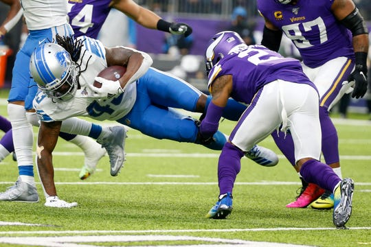 Detroit Lions running back Bo Scarbrough is tackled by Minnesota Vikings cornerback Mike Hughes, right, during the first half Sunday, Dec. 8, 2019, in Minneapolis.