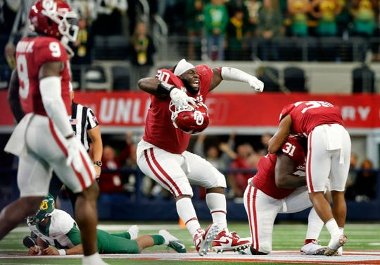 Oklahoma Sooners defensive lineman Neville Gallimore (90) and his teammates celebrate their win over the Baylor Bears in the Big 12 Championship.