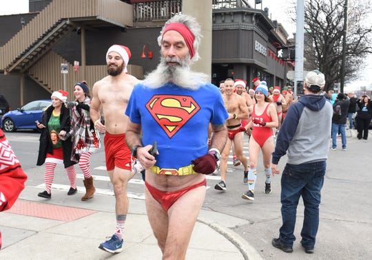 Participants run along Jefferson Avenue for the start of the annual Detroit Santa Speedo Run in Detroit on Sunday, December 8, 2019.