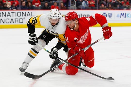 Penguins defenseman Marcus Pettersson and Red Wings center Luke Glendening fight for the puck in the second period.