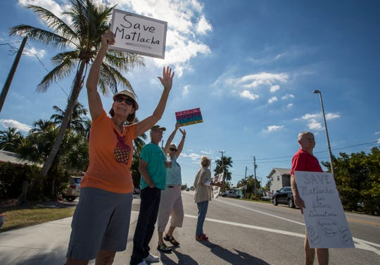 Protesters gather along the Matlacha bridge last month, opposing the possible annexation of the island by the city of Cape Coral.