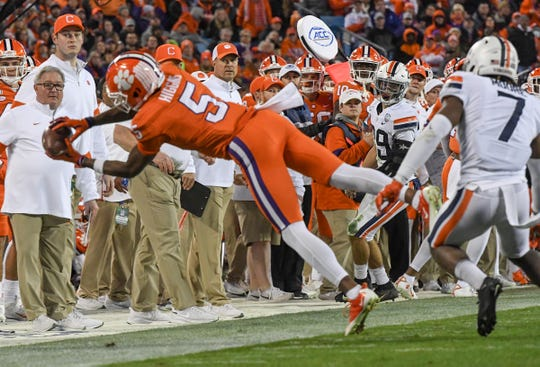 Clemson wide receiver Tee Higgins (5) catches a pass as the sideline watches during the second quarter of the ACC Championship game at the Bank of America Stadium in Charlotte Saturday, Dec. 7, 2019.