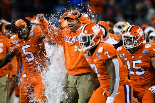 Clemson players soak head coach Dabo Swinney in the final moments of the ACC Championship game against Virginia at the Bank of America Stadium Saturday, Dec. 7, 2019.