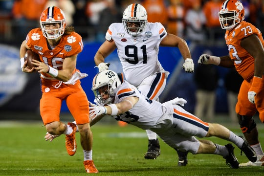 Clemson quarterback Trevor Lawrence (16) attempts to evade Virginia Zane Zandier (33) during the ACC Championship game at the Bank of America Stadium Saturday, Dec. 7, 2019.