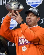 Clemson Head Coach Dabo Swinney celebrates with the ACC football championship trophy after the ACC Championship game in Charlotte, N.C. Saturday, December 7, 2019.