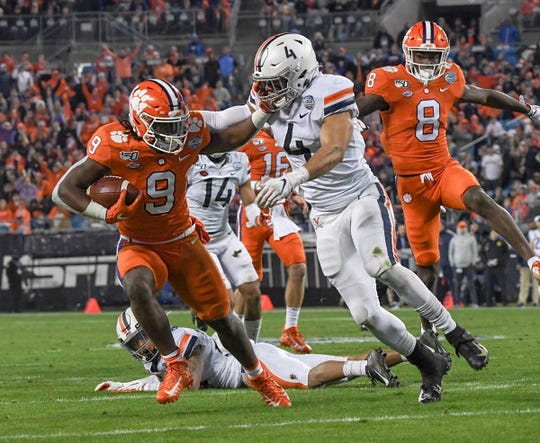 Clemson running back Travis Etienne (9) pushes off of Virginia linebacker Jordan Mack (4) on his way to a 26-yard touchdown during the second quarter of the ACC Championship game at the Bank of America Stadium in Charlotte Saturday, Dec. 7, 2019.