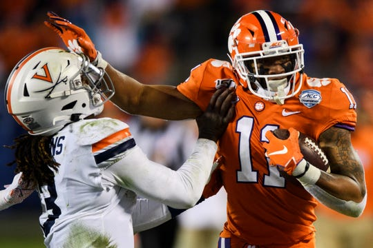 Clemson safety Isaiah Simmons (11) pushes past Virginia quarterback Bryce Perkins (3) after intercepting the ball during the ACC Championship game at the Bank of America Stadium Saturday, Dec. 7, 2019.
