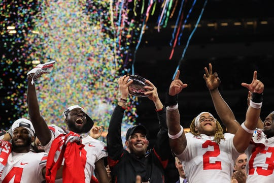 Dec 7, 2019; Indianapolis, IN, USA; Ohio State Buckeyes head coach Ryan Day (center) holds the Big Ten Championship Trophy as he celebrates with Ohio State Buckeyes wide receiver K.J. Hill (left), wide receiver Binjimen Victor (middle left), and defensive end Chase Young (middle right) after defeating the Wisconsin Badgers in the 2019 Big Ten Championship Game at Lucas Oil Stadium.