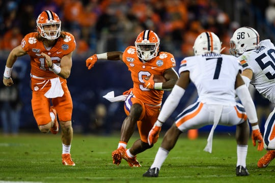 Clemson running back Travis Etienne (9) attempts to evade Virginia defense during the ACC Championship game at the Bank of America Stadium Saturday, Dec. 7, 2019.