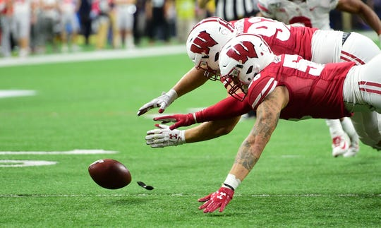 Dec 7, 2019; Indianapolis, IN, USA;     Wisconsin Badgers defensive end Matt Henningden (92) and linebacker Tyler Johnson (59) recover a Ohio State fumble inside the 5 yard line  during the first half in the 2019 Big Ten Championship Game at Lucas Oil Stadium.