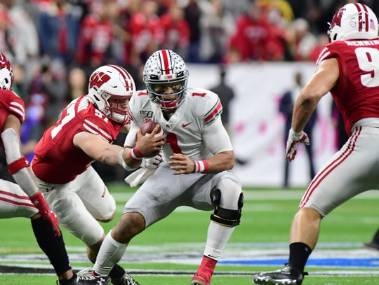 Dec 7, 2019; Indianapolis, IN, USA;  Ohio State Buckeyes quarterback Justin Fields (1) runs out of the pocket and is tackled by Wisconsin Badgers  defensive end Noah Potter (97)  during the first half in the 2019 Big Ten Championship Game at Lucas Oil Stadium.