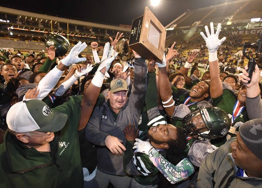 The West Point Green Wave and head coach Chris Chambless celebrate with the Class 5A trophy at the MHSAA State Football Championships at M.M. Roberts Stadium on the University of Southern Mississippi campus in Hattiesburg on Saturday, December 7, 2019.
