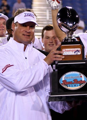 Florida Atlantic Owls head coach Lane Kiffin holds up the trophy after defeating the Akron Zips in the 2017 Boca Raton Bowl at FAU Stadium.