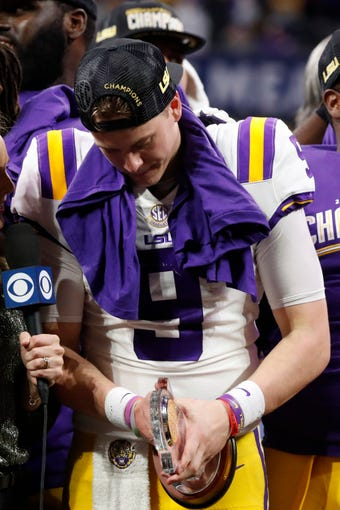 LSU quarterback Joe Burrow (9) holds his MVP trophy after the Southeastern Conference championship NCAA college football game against Georgia, Saturday, Dec. 7, 2019, in Atlanta. LSU won 37-10. (AP Photo/John Bazemore)