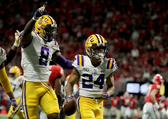 Dec 7, 2019; Atlanta, GA, USA; LSU Tigers cornerback Derek Stingley Jr. (24) celebrates his interception with linebacker Patrick Queen (8) in the third quarter against the Georgia Bulldogs of the 2019 SEC Championship Game at Mercedes-Benz Stadium. Mandatory Credit: Jason Getz-USA TODAY Sports