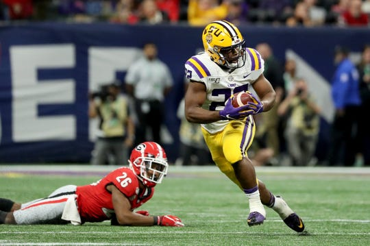 Dec 7, 2019; Atlanta, GA, USA; LSU Tigers running back Clyde Edwards-Helaire (22) runs against Georgia Bulldogs defensive back Tyrique McGhee (26) in the second half in the 2019 SEC Championship Game at Mercedes-Benz Stadium. Mandatory Credit: Jason Getz-USA TODAY Sports