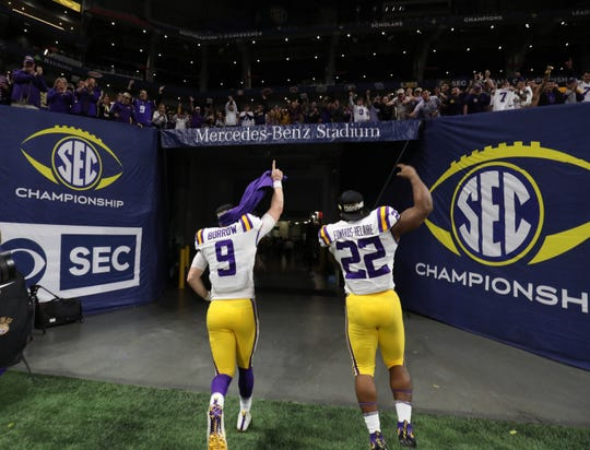 Dec 7, 2019; Atlanta, GA, USA; LSU Tigers quarterback Joe Burrow (9) and running back Clyde Edwards-Helaire (22) celebrate their win against the Georgia Bulldogs in the 2019 SEC Championship Game at Mercedes-Benz Stadium. Mandatory Credit: Jason Getz-USA TODAY Sports