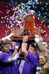 Dec 7, 2019; Atlanta, GA, USA; LSU Tigers hoist the trophy after their 37-10 victory over the Georgia Bulldogs in the 2019 SEC Championship Game at Mercedes-Benz Stadium. Mandatory Credit: John David Mercer-USA TODAY Sports