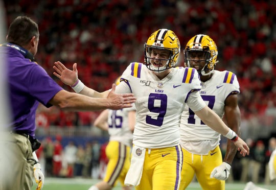 Dec 7, 2019; Atlanta, GA, USA; LSU Tigers quarterback Joe Burrow (9) celebrates his fourth passing touchdown with head coach Ed Orgeron in the third quarter against Georgia Bulldogs in the 2019 SEC Championship Game at Mercedes-Benz Stadium. Mandatory Credit: Jason Getz-USA TODAY Sports