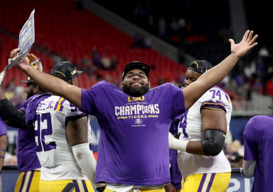 Dec 7, 2019; Atlanta, GA, USA; LSU Tigers defensive lineman Rashard Lawrence (90) celebrates their win against the Georgia Bulldogs in the 2019 SEC Championship Game at Mercedes-Benz Stadium. Mandatory Credit: Jason Getz-USA TODAY Sports
