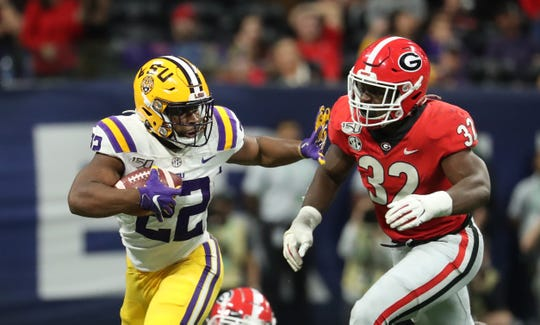 Dec 7, 2019; Atlanta, GA, USA; LSU Tigers running back Clyde Edwards-Helaire (22) runs against Georgia Bulldogs linebacker Monty Rice (32) in the second half in the 2019 SEC Championship Game at Mercedes-Benz Stadium. Mandatory Credit: Jason Getz-USA TODAY Sports