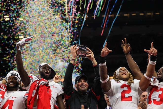 Ohio State coach Ryan Day holds up the Big Ten Championship trophy as he celebrates the 34-21 win over Wisconsin with, left to right, K.J. Hill, Binjimen Victor and Chase Young.