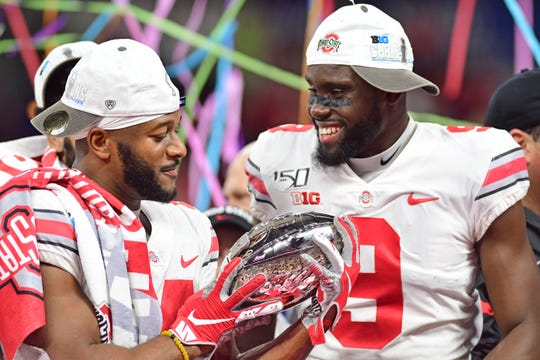 Ohio State receivers K.J. Hill and Binjimen Victor celebrate after the Buckeyes beat Wisconsin 34-21 to win their third straight Big Ten title