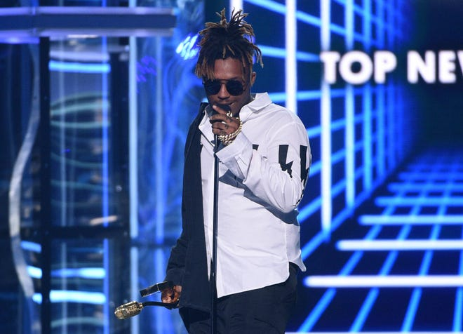 """FILE - In this May 1, 2019, file photo, Juice WRLD accepts the award for top new artist at the Billboard Music Awards at the MGM Grand Garden Arena in Las Vegas. The Chicago-area rapper, whose real name is Jarad A. Higgins, was pronounced dead Sunday, Dec. 8, after a """"medical emergency'' at Chicago's Midway International Airport, according to authorities. Chicago police said they're conducting a death investigation."""