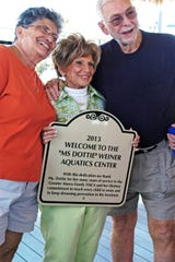 """Friends Carol & Dick Polinkski pose with Dottie Weiner as she cradles the new sign dedicated to the """"Ms Dottie"""" Weiner Aquatic Center on April 27, 2013."""