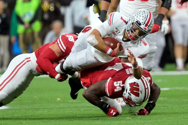 Ohio State quarterback Justin Fields is tackled by Wisconsin's Chris Orr (54) and Zack Baun during the first half.