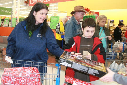 Patricia Kirkwood (left) and her son James Denning, a seventh grader at Pinkston Middle School, hand over their selections during Saturday's Shop With a Cop event at the Mountain Home Walmart. Members of the Junior Auxiliary of Mountain Home provided free gift wrapping to the approximately 95 young people who shopped Saturday, along with a shopping cart of food for their family's Christmas meal.