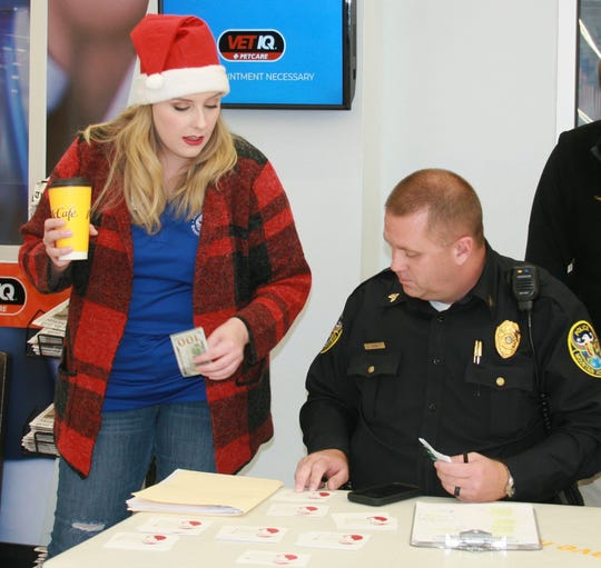 Junior Auxiliary of Mountain Home member and chairwoman of this year's Food for Families event, Emily Jordan (left), and Mountain Home Police Sgt. Bryan Corbett, who also serves as the vice president of the Fraternal Order of Police Lodge #45 of Mountain Home, coordinate their efforts during Saturday's Shop With a Cop event at the Mountain Home Walmart. Approximately 95 kids from Baxter County were each given a $100 gift card to buy Christmas presents for themselves and family members as part of the annual program.