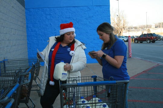 Junior Auxiliary of Mountain Home members Courtney Jackson (left) and Jilliam Bemis load up shopping carts as part of the organization's Food for Families event on Saturday at the Mountain Home Walmart. Food for Families provided Christmas dinner staples for the roughly 40 families who also participated in the annual Shop With a Cop event sponsored by the Fraternal Order of Police Lodge #45 of Mountain Home.