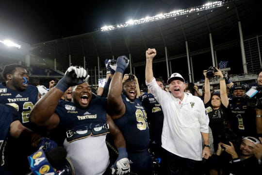 FIU head coach Butch Davis celebrates with his players after defeating Miami 30-24 in an NCAA college football game, Saturday, Nov. 23, 2019, in Miami. (AP Photo/Lynne Sladky)