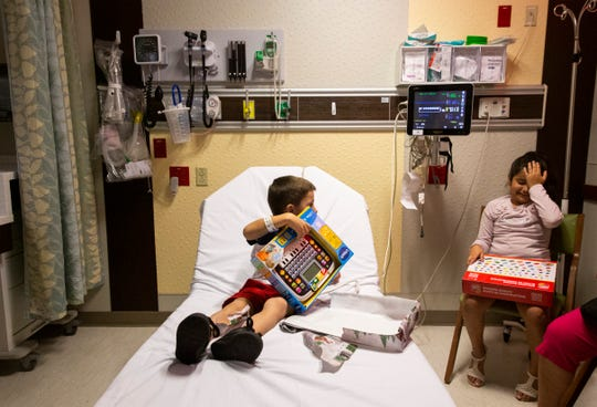 Matthew Gonzales, 5, left, shows off his gift to Melanie Gonzales, 8, right, on Sunday, December 8, 2019, at North Naples Hospital Pediatric Emergency Department.