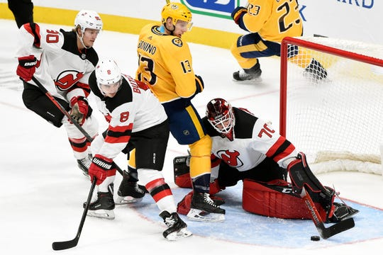 New Jersey Devils goaltender Louis Domingue (70) stops a shot in front Nashville Predators center Nick Bonino (13) as defenseman Will Butcher (8) looks for the puck during the third period of an NHL hockey game Saturday, Dec. 7, 2019, in Nashville, Tenn. The Predators won 6-4. (AP Photo/Mark Zaleski)