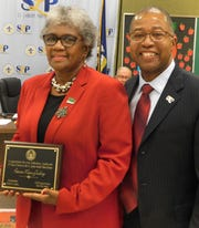 Longtime St. Landry Parish parent and family engagement coordinator Patricia Mason-Guillory is presented with a retirement plaque from Superintendent Patrick Jenkins on Thursday night. Mason-Guillory is retiring from the school district after working there for 46 years.