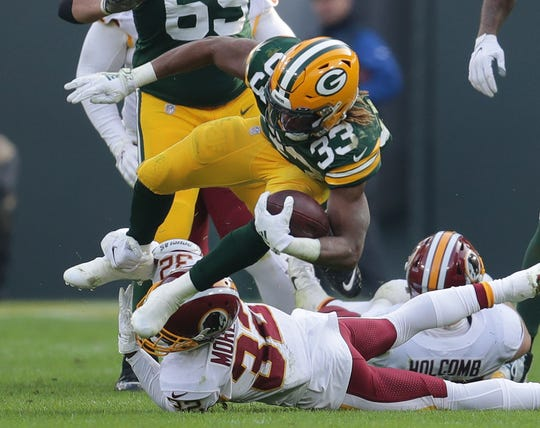 Green Bay Packers running back Aaron Jones (33) leaps over a tackling Washington Redskins cornerback Jimmy Moreland (32) during the 2nd half of the Green Bay Packers 20-15 win over the Washington Redskins at Lambeau Field in Green Bay  on Sunday, Dec. 8, 2019.  Photo by Mike De Sisti/Milwaukee Journal Sentinel
