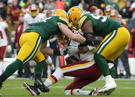 Green Bay Packers nose tackle Kenny Clark (97) and  linebacker Kyler Fackrell (51) sack Washington Redskins quarterback Dwayne Haskins (7) during their football game Sunday, December 8, 2019, at Lambeau Field in Green Bay, Wis. Wm. Glasheen/USA TODAY NETWORK-Wisconsin