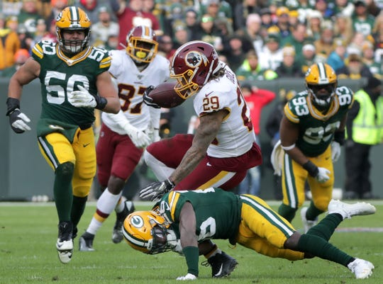 Green Bay Packers free safety Darnell Savage (26) tackles Washington Redskins running back Derrius Guice (29) during their football game Sunday, December 8, 2019, at Lambeau Field in Green Bay, Wis. 