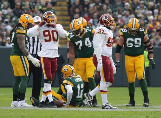 Green Bay Packers quarterback Aaron Rodgers (12) sits on the ground after he is sacked by Washington Redskins nose tackle Daron Payne (94) during the first half of the Green Bay Packers football game against the Washington Redskins at Lambeau Field in Green Bay  on Sunday, Dec. 8, 2019.  Photo by Mike De Sisti/Milwaukee Journal Sentinel