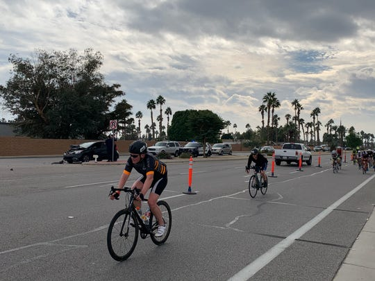 Ironman triathlon competitors pass a traffic collision on Jefferson Street in La Quinta on Sunday, Dec. 8, 2019. The bicycle course was moved to Jefferson after the 2018 event caused gridlock on Washington Street.