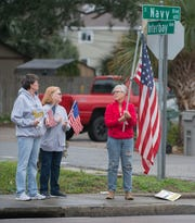 Mourners wait for the hearse processional on Navy Boulevard on its way to NAS Pensacola Sunday, Dec. 8, 2019.
