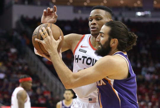 Dec 7, 2019; Houston, TX, USA; Phoenix Suns guard Ricky Rubio (11) drives against Houston Rockets guard Russell Westbrook (0) in the first quarter at Toyota Center. Mandatory Credit: Thomas B. Shea-USA TODAY Sports