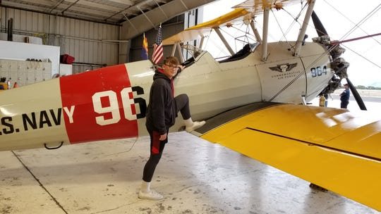 Dylan Hoffman, 14, poses on a restored Boeing-Stearman, an aircraft that was traditionally used to train cadets on how to fly during World War II, at the CAF Airbase Arizona Museum on Dec. 7, 2019. Hoffman was replicating a photograph of his great-grandfather posing on a Stearman during WWII.