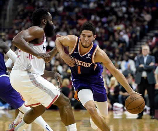 Phoenix Suns' Devin Booker (1) drives toward the basket as Houston Rockets' James Harden defends during the second half of an NBA basketball game Saturday, Dec. 7, 2019, in Houston. The Rockets won 115-109. (AP Photo/David J. Phillip)