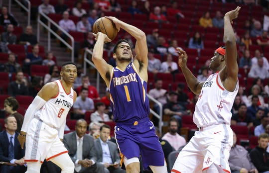 Dec 7, 2019; Houston, TX, USA; Phoenix Suns guard Devin Booker (1) shoots against Houston Rockets guard Russell Westbrook (0) and forward Danuel House Jr. (4) in the first quarter at Toyota Center. Mandatory Credit: Thomas B. Shea-USA TODAY Sports