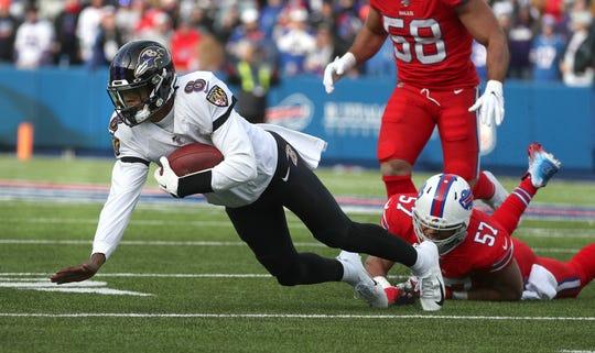 Ravens quarterback Lamar Jackson is tripped up by Bills Lorenzo Alexander after a short gain.
